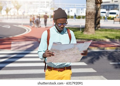 Outdoor urban shot of serious dark-skinned European traveler in stylish clothing standing in the middle of street with city guide, trying to find way to his hotel while got lost. Travel and vacations