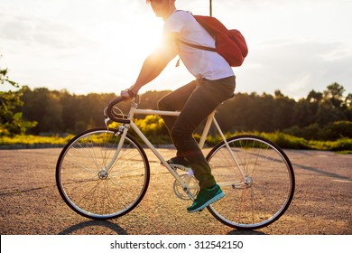 Outdoor urban style summer portrait of young handsome hipster man riding bicycle having fun on sunset