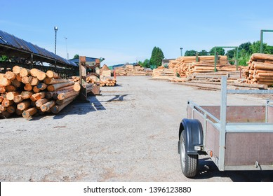 Outdoor, utility trailer for transport at sawmill in europe with background stacking the logs ,green forest ,blue sky and clouds. industrial wood yard with stacks of new wood poles.