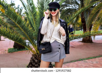 Outdoor vacation fashion portrait of beauty student woman posing at Spanish barcelona street with palm trees, spring street style, sexy outfit , bag, skirt and vintage retro sunglasses. Soft colors.