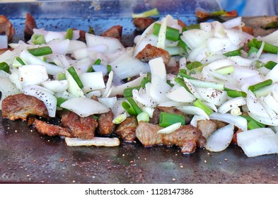 An outdoor vendor cooks meat, onions and leeks on a Teppanyaki griddle