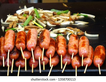 An outdoor vendor roasts fresh sausages and fries pork and leaks