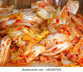 An outdoor vendor sells Kimchi, that is fermented spicy cabbage