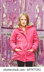 Outdoor vertical portrait of cute 9 year old little girl wearing pink winter coat, standing next to purple background