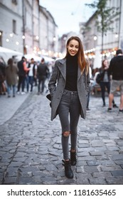 Outdoor vertical portrait of young beautiful fashionable brunette woman posing in street at autumn. Model wearing stylish gray coat, skinny jeans and black golf. Autumn Female fashion concept, city