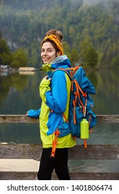 Outdoor vertical shot of glad backpacker wears anorak, poses with big rucksack against small calm river and green trees in background, enjoys fresh air during morning walk, enjoys beautiful scenery