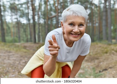 Outdoor view of energetic joyful female pensioner in sports clothes leaning forward, smiling and pointing fore finger at camera, inviting you to join her in morning run, having break during workout