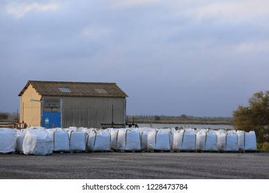 Outdoor view of the factory buildings of the salins du midi, located at aigues mortes marshes, gard department, France. November, 11, 2018. White bags rows and piles of salt ont the ground visible.