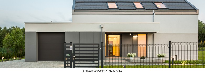 Outdoor view of new stylish home with fence and stone driveway, panorama