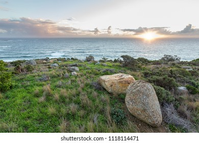 outdoor view of the ocean setting rising sun with green grass and large rocks in the foreground