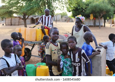 Outdoor view of people filling their plastic cans with water from the fountain in the village of Thiékène, Saint Louis region, Northern Senegal, West Africa. October, 23, 2019. Woman and children.