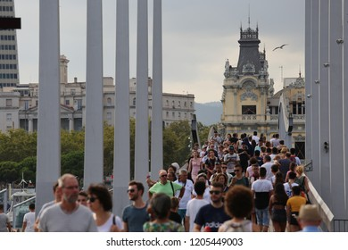 Outdoor view of people walking on the wooden bridge called la rambla de mar at port vell district, In Barcelona city, catalonia, Spain.  August, 27, 2018. Scene with crowd in the spanish town.