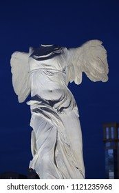 Outdoor view of samothrace victory statue, located in antigone district, Montpellier city, France. June, 8, 2018. White stone monument representing a winged woman without head. Dark sky in background
