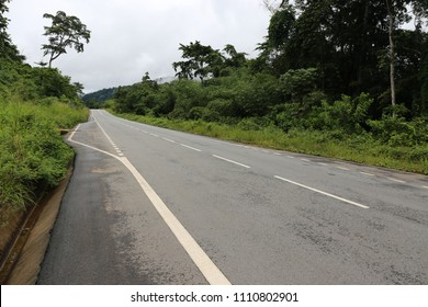Outdoor view of a straight asphalt road in Gabon, tropical country, Africa. Luxurious vegetation with high trees on each side of the large way. White traffic lines. Clear blue sky in background.
