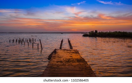 Outdoor view of wooden pier and Bacalar Lagoon suring a gorgeous sunset view in Mayan Mexico at Quintana roo, seven color lake