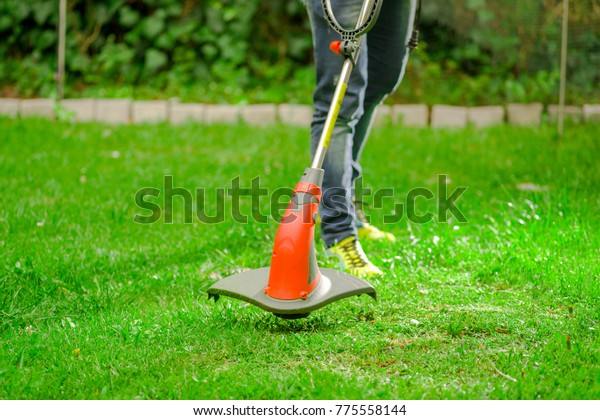 Outdoor view of young worker wearing jeans and using a lawn trimmer mower cutting grass in a blurred nature background