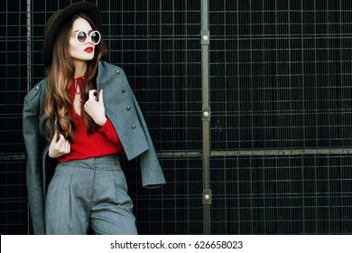 Outdoor waist up portrait of beautiful woman posing on street. Model wearing stylish red, grey classic clothes, wide-brimmed hat, round sunglasses. Female fashion concept. Copy, empty space for text