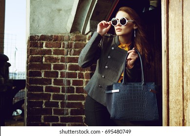 Outdoor waist up portrait of beautiful young woman posing near wall, looking aside, holding big blue bag. Model wearing stylish round sunglasses, clothes. Female fashion. Copy, empty space for text