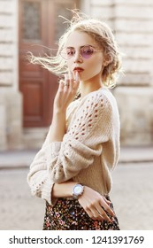 Outdoor waist up portrait of young beautiful fashionable girl wearing purple sunglasses, knitted beige sweater, wrist watch, posing in street of european city.