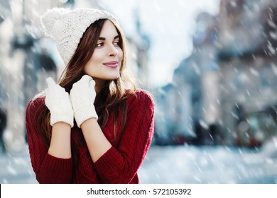 Outdoor waist up portrait. Young beautiful happy smiling girl walking on street. Model looking aside, wearing stylish sweater, hat, gloves. City lifestyle. Magic snowfall. Empty, copy space for text