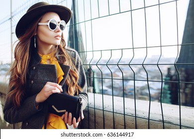 Outdoor waist up portrait of young beautiful woman with long hair. Model wearing stylish hat, sunglasses, clothes, holding small bag. City lifestyle. Female fashion concept. Copy, empty space for text