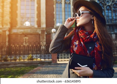 Outdoor waist up portrait of young beautiful woman posing on street. Model looking aside, wearing stylish hat, sunglasses, scarf, holding small bag. Sunset. Female fashion. Copy, empty space for text