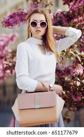 Outdoor waist up portrait of young beautiful girl posing in street. Model wearing stylish round sunglasses, white shirt, wrist watch, holding pink bag, handbag. City lifestyle. Female fashion concept