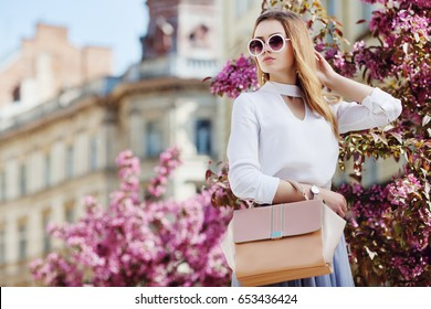 Outdoor waist up portrait of young beautiful girl posing in street. Model wearing stylish sunglasses, white shirt, holding pink bag. City lifestyle. Female fashion concept.