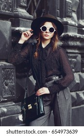Outdoor waist up portrait of young beautiful fashionable girl posing in street. Model wearing stylish clothes, round sunglasses, hat, holding bag, briefcase. City lifestyle. Female fashion concept