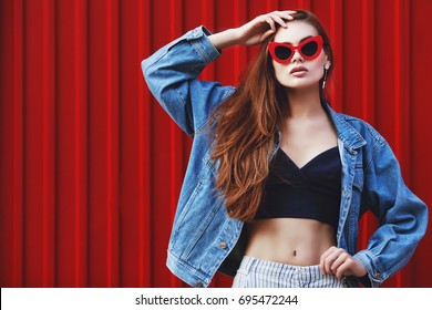 Outdoor waist up portrait of young beautiful fashionable girl posing in street. Model wearing stylish jeans jacket, sunglasses. Red background. Female fashion concept. Copy, empty space for text