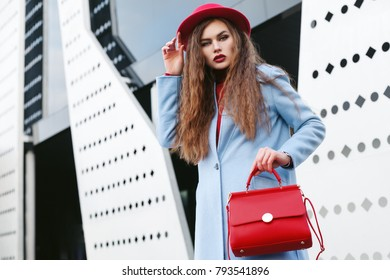 Outdoor waist up portrait of young beautiful fashionable woman posing in street. Model wearing light blue coat, red hat, holding trapeze handbag. Female fashion concept. Copy, empty space for text