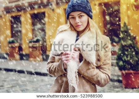 Outdoor waist up portrait of young beautiful fashionable woman posing on street. Model wearing stylish winter fake fur coat and beanie hat, looking at camera.  Magic snowfall effect. Day light