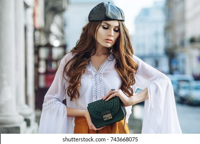 Outdoor waist up portrait of young fashionable woman holding small green bag, posing in street. Model with beautiful long hair. Lady wearing stylish clothes, leather beret. Female fashion concept