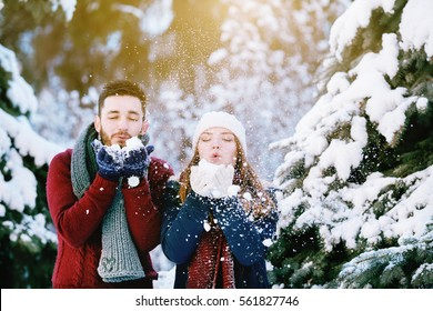 Outdoor waist up portrait of young happy beautiful couple blowing snow. Models wearing stylish warm winter clothes. Day light, sunny weather. Park with green fir-trees  on background