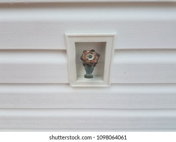 outdoor water spigot and white siding