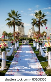 Outdoor wedding by the beach with palm trees, rose petals on isl
