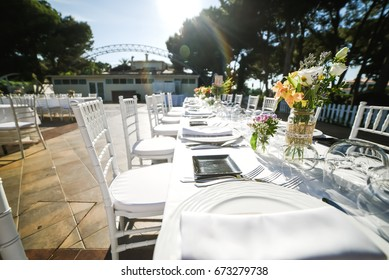 Outdoor wedding celebration in a restaurant. Festive table setting, catering. Wedding in rustic style in summer, floral decorations.