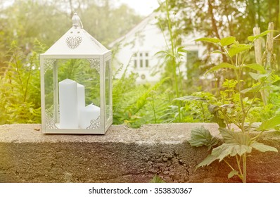 Outdoor wedding day in the romantic greenhouse - simple detail of isolated lantern with white candle inside. Nature green background.