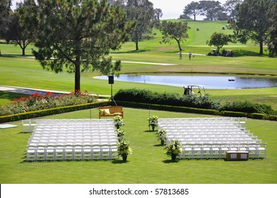 Outdoor wedding reception venue set up with white chairs and golf course view