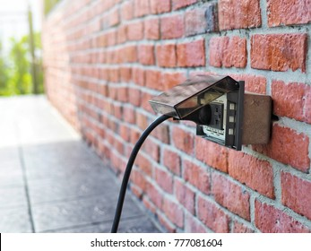 Outdoor white Electrical Outlet with cover on brick wall