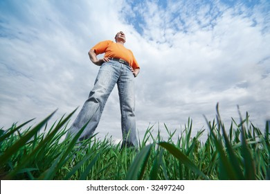 Outdoor wide-angle portrait of a tall man in jeans on blue sky and green grass background