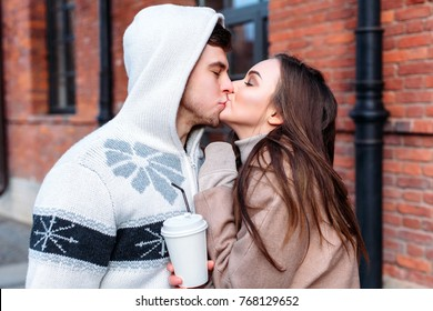 Outdoor winter closeup portrait of young stylish beautiful kissing couple in love posing with cup of coffee
