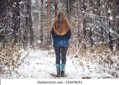 Outdoor winter forest landscape with white snow falling. Winter portrait photography. Winter girl standing backwards in winter forest outdoor. Woman in deep woods snow, nature landscape photography