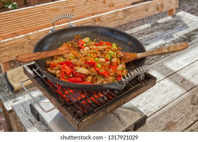 Outdoor wok cooking with chicken meat and vegetables in a black wok on a charcoal grill