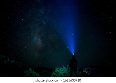 Outdoor Woman Silhouette with Head Torch looks at the Milky Way