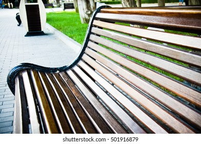 Outdoor wooden bench taken at the seat level to give a different viewpoint. Bench seat Wooden surface. Empty Blank Old wooden bench in a shady area of the garden or the park.Seating for relax in park