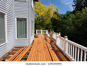 Outdoor wooden deck being remodeled with new red cedar wood floor boards being installed