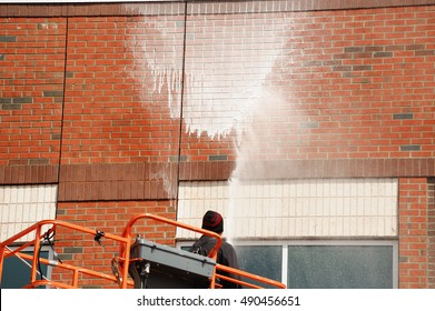 outdoor worker cleaning the exterior wall of building through pressure water