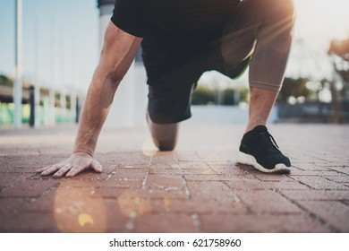 Outdoor Workout lifestyle concept.Young man doing stretch exercises muscles before training.Muscular athlete exercising outside in sunny park. Blurred background.Horizontal