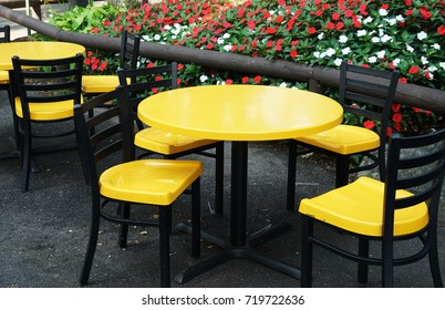 Outdoor yellow round table near flowerbed